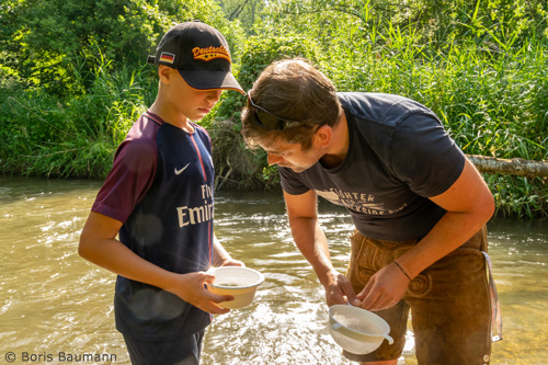 "Jugendwart begutachtet ""Fangergebnisse"" eines Schülers. Fischer machen Schule."